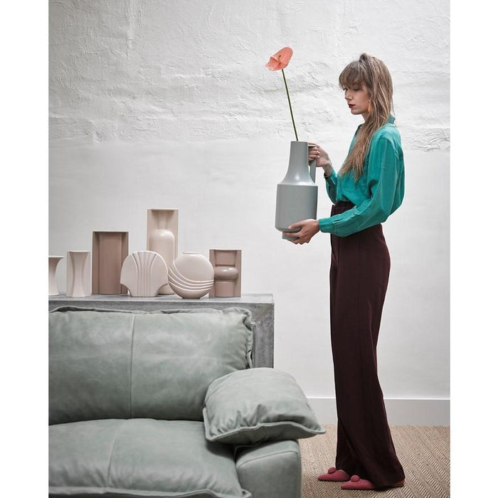 lady with green sweater who is holding a ceramic green vase with one handle