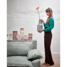 group of vases together in euth tone colors and lady in green blouse