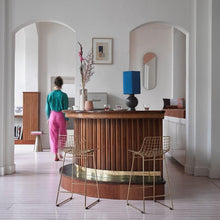 bar with brass counter stools and a terracotto flower pot on top of bar