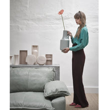 group of earthenware flowervases behind sofa and woman holding green vase