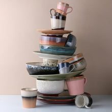 artsy stack of pastel colored ceramic plates, bowls and mugs