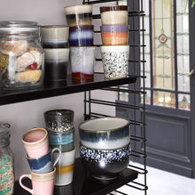 open shelving with all kinds of different HK living USA ceramic mugs and bowls in bold colors