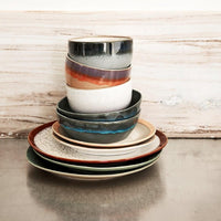 stack of ceramic plates, bowls and side plates in 70's style colors