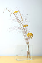 glass staircase vase with yellow flowers