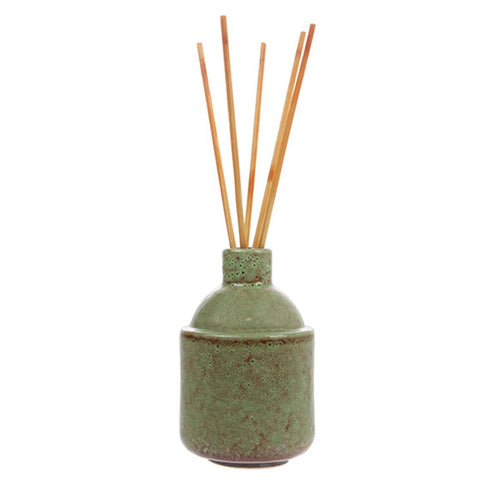 green ceramic pot with scented oil and wooden sticks