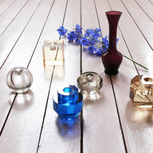 group of crystal candle stick holders in varios colors together on a wooden floor