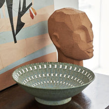 abstract head sculpture in terracotta next to a bowl