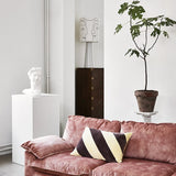 greek replica statue of Apollo as indoor sculpture in white on pedestal with pink sofa