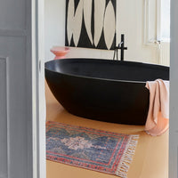 black oval shaped bath tub with red and blue rug