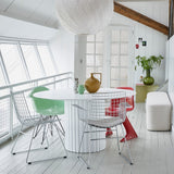 dining room with white pendant light, white walls, white lobby bench and a red chair for a pop of color