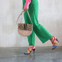 blush colored shoulder bag with panther print and golden speckles, carried by a woman with green pants