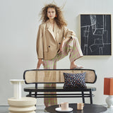 retro bench with cane webbing and woman with curly hair