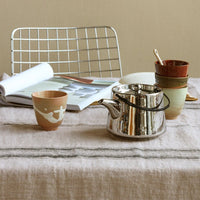 silver colored stoneware teap ot on a linen table cloth with ceramic tea cups in earth tones