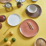 yellow countertop with ceramic plates in cherry, white and brown tones and a set of ceramic teaspoons in pastel colors