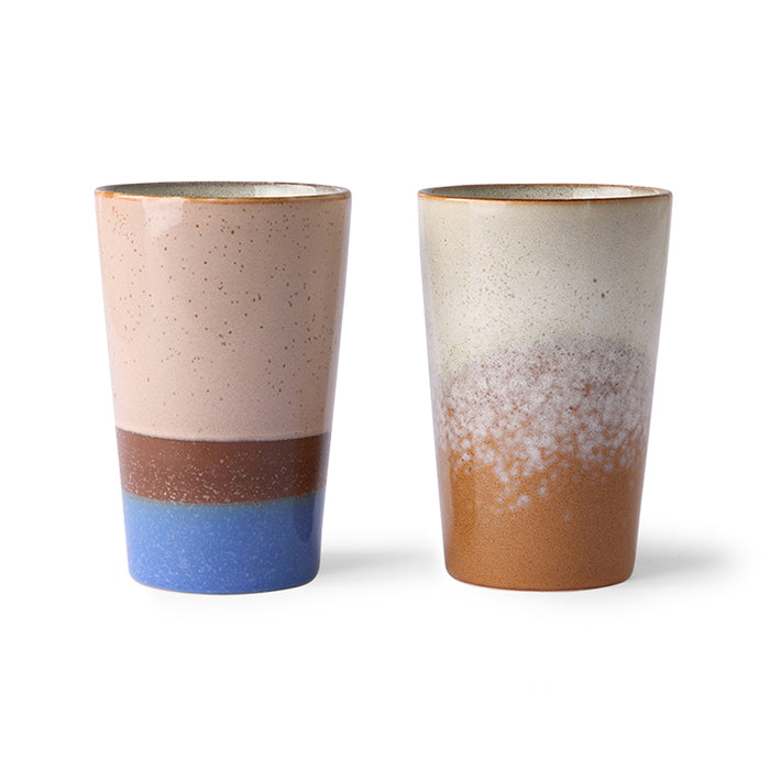 two slim, tall ceramic mugs in blue and brown colors