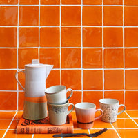 orange back splash with funky ceramic cups
