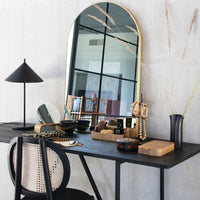 vanity with arch shaped mirror in a brass frame