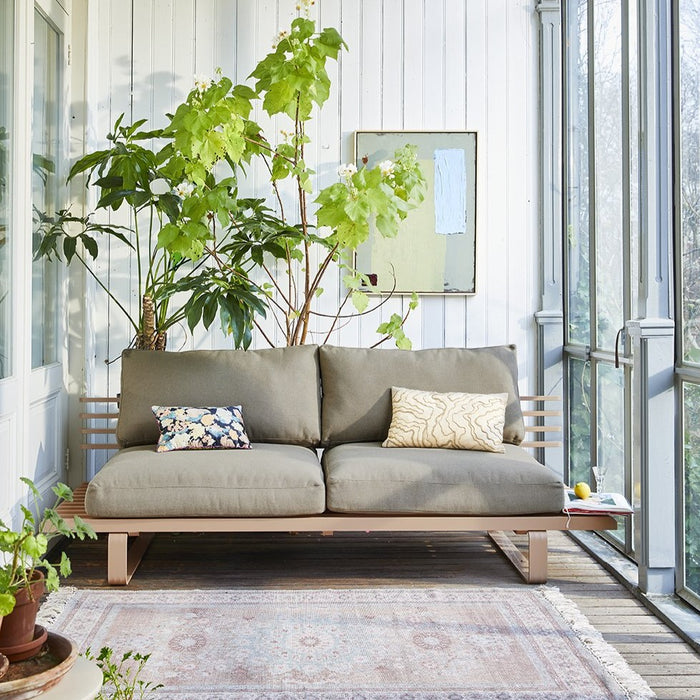 sun room with outdoor bench with cushions and an abstract painting on the wall