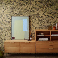 Danish style cabinet with drawers and an abstract painting in calming colors against a flower wallpaper