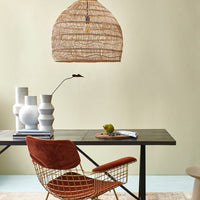 wicker basket light hanging above a black table with a brass dining chair with velvet covering