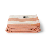 folded striped beach blanket with peach stripes