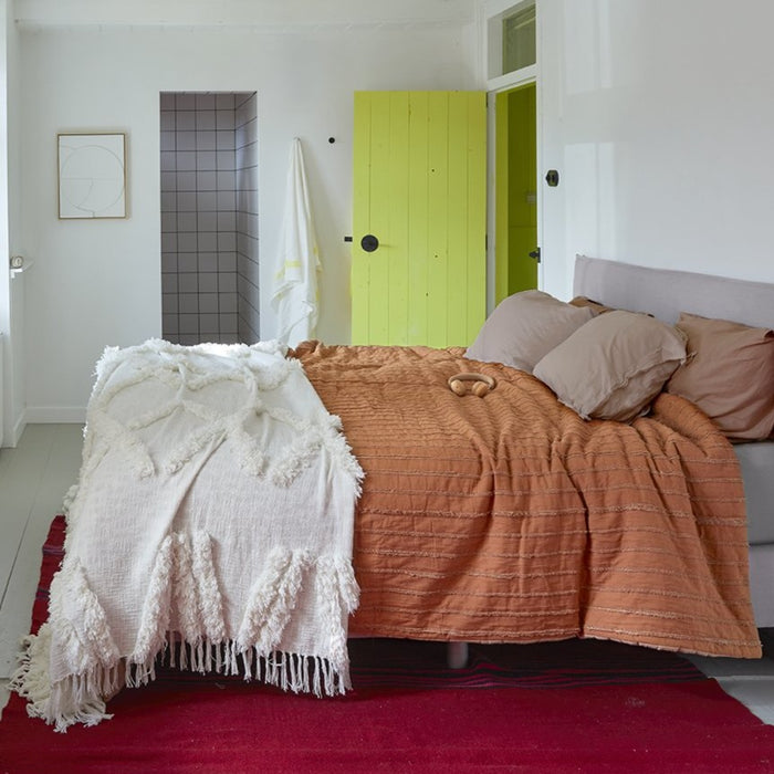 bedroom with yellow door and two different bedspreads in oranfge and white