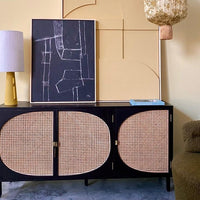 sideboard with cane webbing details and abstract art in black and yellow