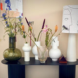black oval console table with table lamp and flower vases