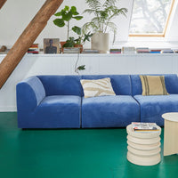 living room with a green floor, blue sofa and natural linen pillows in light colors