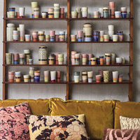 collection of colorful, ceramic mugs in an open shelving wooden cabinet