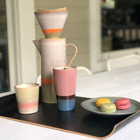 coffee pot and matching filter on a black wooden tray with mugs in happy colors