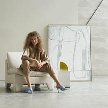 woman on lounge chair with brutalism painting against wall