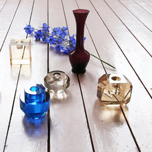 glass candlestick holders on a wooden floor