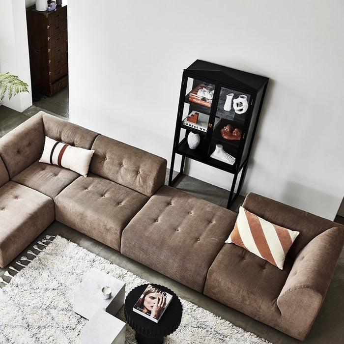 element sofa in corner position with striped pillow and showcase cabinet