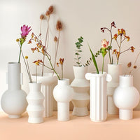 white speckled vases on peach colored table