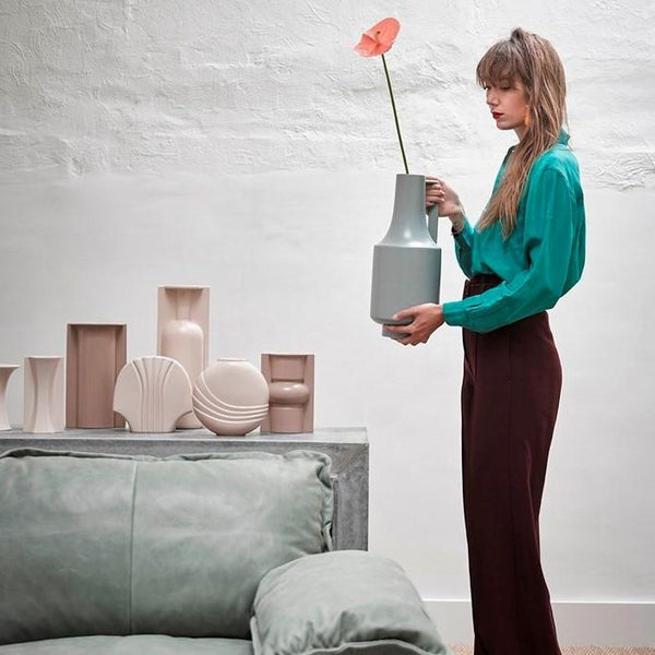 group of vases in earth tones and woman holding a green vase