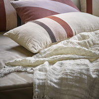 white linen coverlet with striped pillows