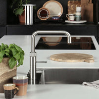 black kitchen with white counter top en dinner plates made of earth colored stoneware in rack