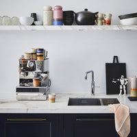 kitchen with marble counter top and marble shelving with 70's ceramics by design brand HKliving