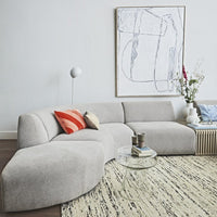 modern living room with grey sectional sofa and glass side table with set of latte mugs