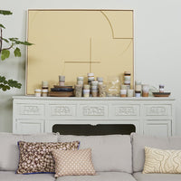 large acoustic relief art panel on a fireplace mantel behind a grey sofa with pillows