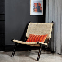 casual lounge chair with a black frame and cane webbing seating and back against a black wall with a modern art work