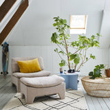 boucle lounge chair with ottoman in pink next to a blue side table and a big green plant behind the chair