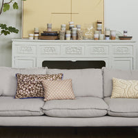 grey retro sofa with a variation of pillows in cream and brown tones