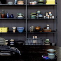black wall with open shelving and colorful ceramics with a 70's design and color