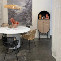 loft with dark cement floor, white dining table with chairs and black oval retro style cabinet