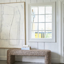 large white abstract art work on shiplap wall with upholstered bench