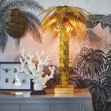 styling with brass palm lamp, artificial coral and brass insects in frame