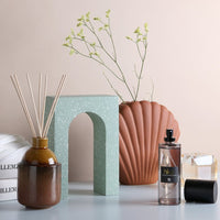 reed diffuser in ceramic vase and mint green terrazzo arch and shell vase in terracotta color