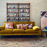 gold ochre velvet sofa with open shelving filed with ceramics